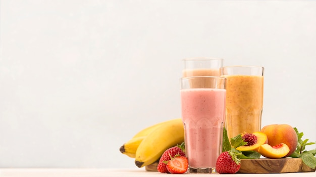 Front view of assortment of milkshakes with strawberry and copy space