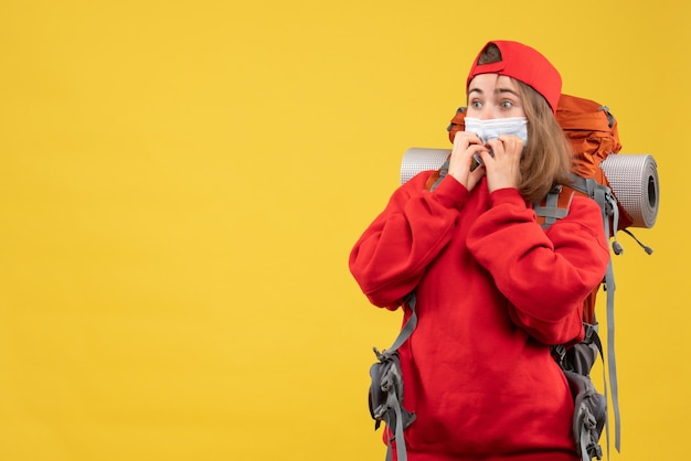 Вид спереди изумленная женщина-турист с рюкзаком и маской
