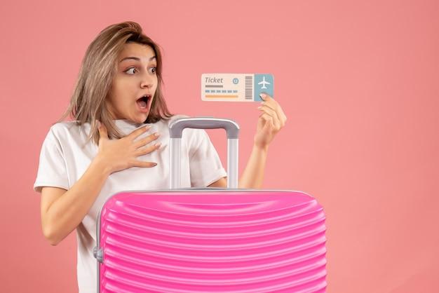 Vista frontale della ragazza stupita con il biglietto rosa della holding della valigia