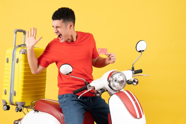 Front view astonished young man on moped holding credit card