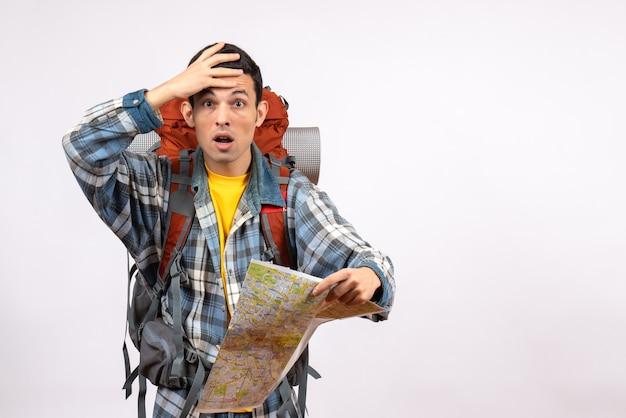 Vista frontale stupito giovane viaggiatore con zaino in possesso di mappa