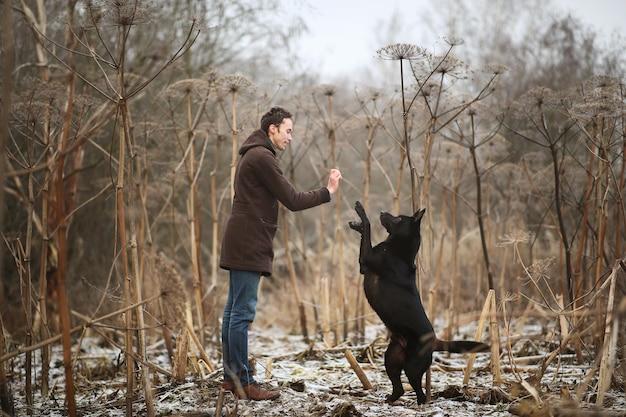 큰 검은 개 야외 훈련 세련된 젊은이의 전면보기
