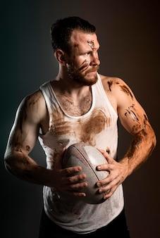 Vista frontale della sfera della holding del giocatore di rugby maschio sporco atletico