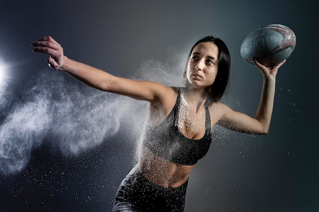 Vista frontale del giocatore di rugby femminile atletico che tiene palla con polvere