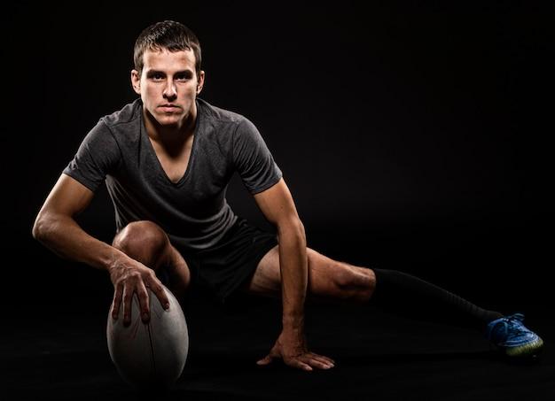 Vista frontale del giocatore di rugby bello atletico che tiene palla con lo spazio della copia