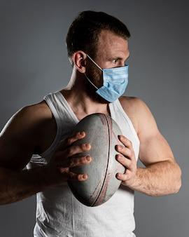 Vista frontale del giocatore di rugby maschile atletico che tiene palla mentre indossa la maschera medica