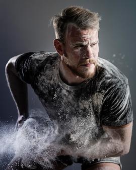 Vista frontale del giocatore di rugby maschio atletico che tiene palla con polvere