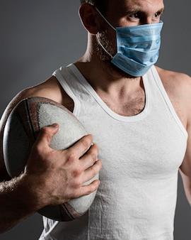 Vista frontale del giocatore di rugby maschio atletico che indossa la maschera medica e che tiene palla