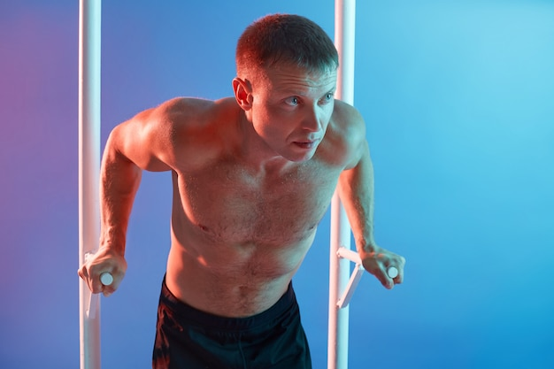Front view of athletic man exercising calisthenics workout