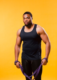 Front view of athletic man in gym outfit with resistance band