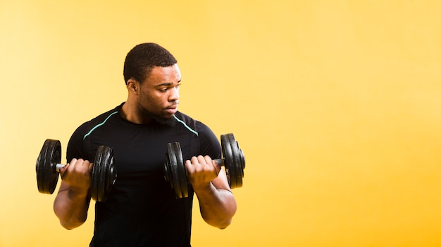 Front view of athletic man holding weights with copy space