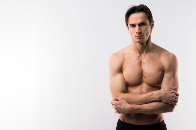Front view of athletic man posing shirtless with copy space