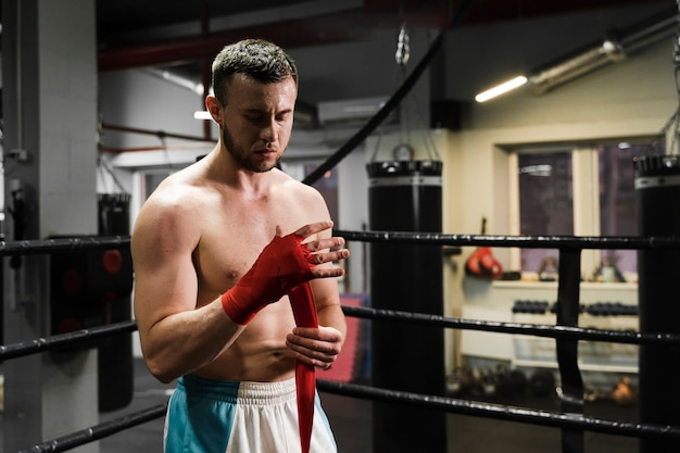 Front view athletic man training in boxing ring