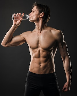 Front view of athletic shirtless man drinking water from bottle