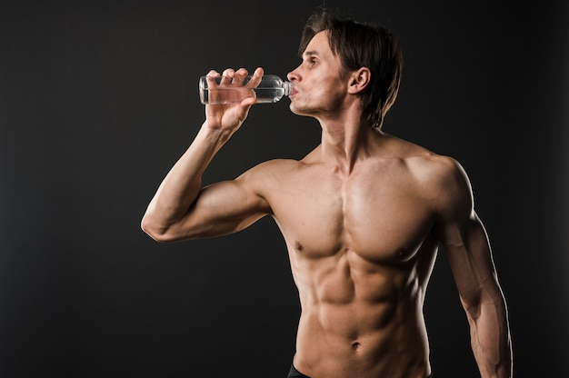 Front view of athletic shirtless man drinking water