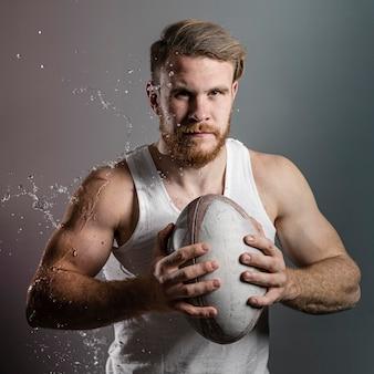 Vista frontale della palla di tenuta del giocatore di rugby maschio bagnato atletico