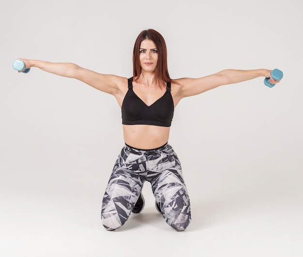Front view of athletic woman exercising with weights