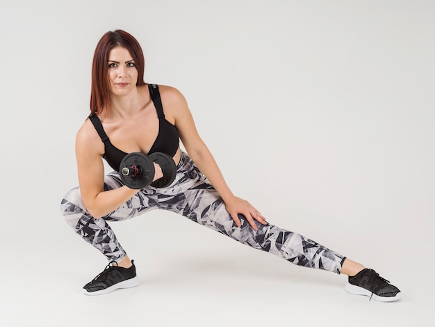 Front view of athletic woman lifting weight and stretching leg
