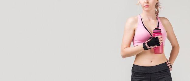 Vista frontale della donna atletica che posa con l'idro boccetta e lo spazio della copia