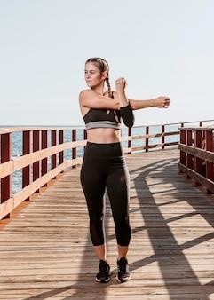 Vista frontale della donna atletica che si estende all'aperto sulla spiaggia
