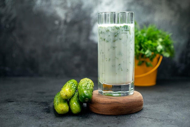 Front view atlama yogurt drink with greens on wood board cucumbers potted plant on grey isolated table copy place