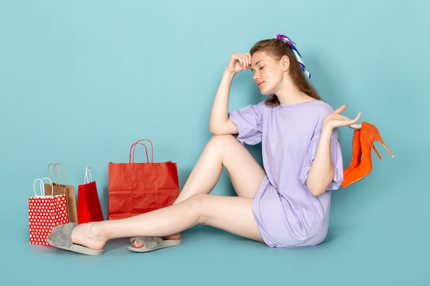 A front view attractive female in blue shirt-dress holding shopping packages and sitting taking off her shoes on blue