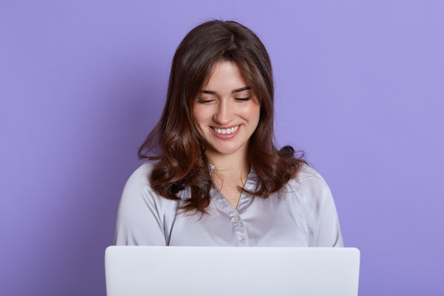 Front view of attractive lady working on laptop and smiling, looks at screen, wearing elegant blouse