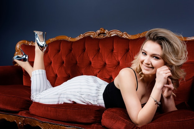 Front view of a attractive smiling woman dressed in a trendy fashion clothing lying on the red sofa on the blue wall background