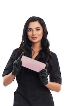 Front view of attractive young beautician in medical uniform and black gloves holding pink cosmetic box