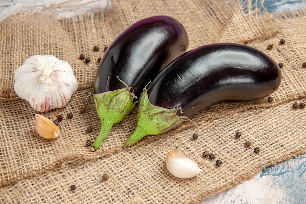 Front view aubergines garlic black pepper on straw tablecloth