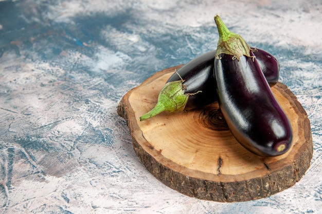 Front view aubergines on tree wood board on blue-white background free place