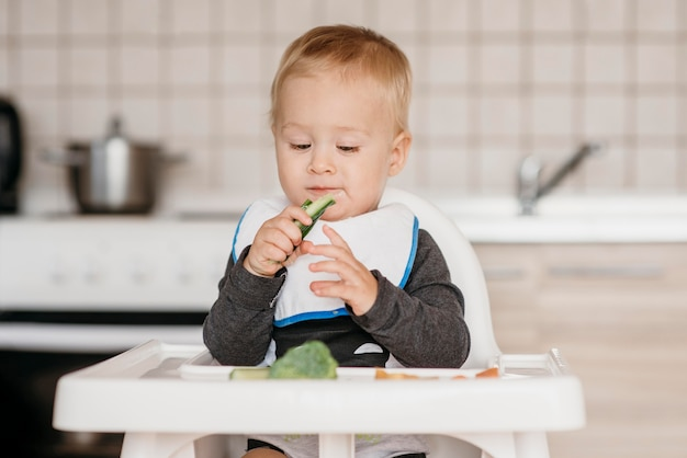 Вид спереди мальчик ест в своем стульчике