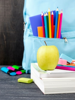 Front view of back to school stationery with apple and colorful pencils