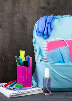 Front view of back to school stationery with backpack and gloves