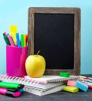 Front view of back to school stationery with pencils and apple