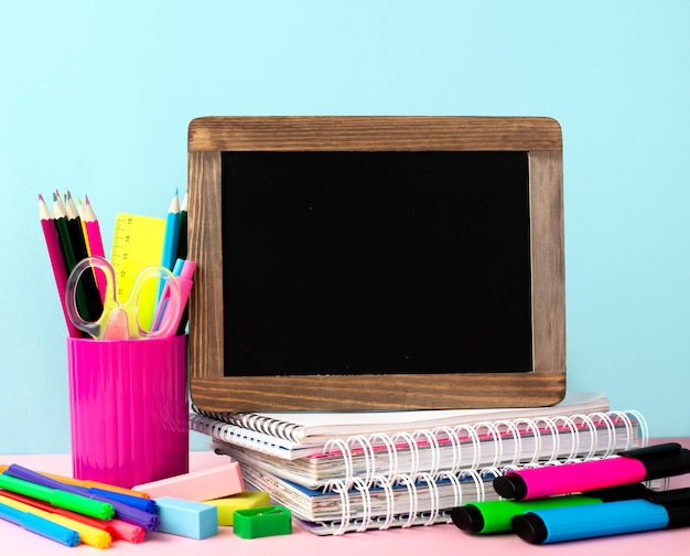 Front view of back to school supplies with blackboard and notebooks