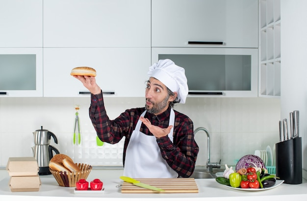 正面図は、キッチンでパンを持ち上げて困惑した男性シェフ