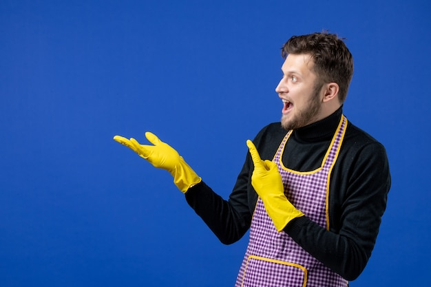 Front view baffled young man pointing at left with fingers on blue space