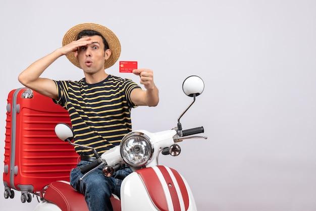 Vista frontale del giovane sconcertato con cappello di paglia sulla carta di credito della holding del ciclomotore