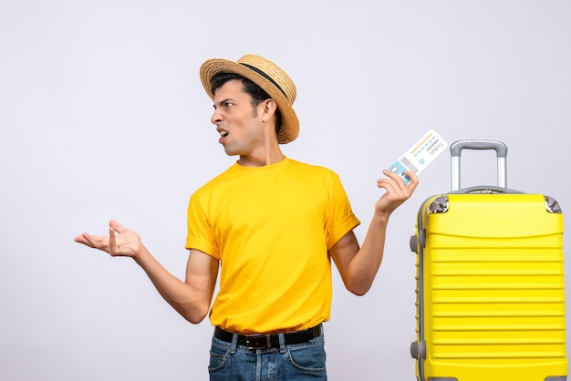 전면보기 티켓을 들고 노란색 가방 근처에 서있는 젊은 관광객 당황
