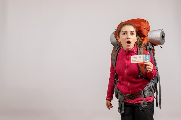 Vista frontale del giovane viaggiatore sconcertato con il grande zaino che sostiene il biglietto di viaggio sul muro grigio