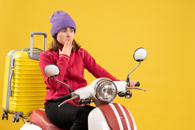 Front view baffled young woman on moped looking at something