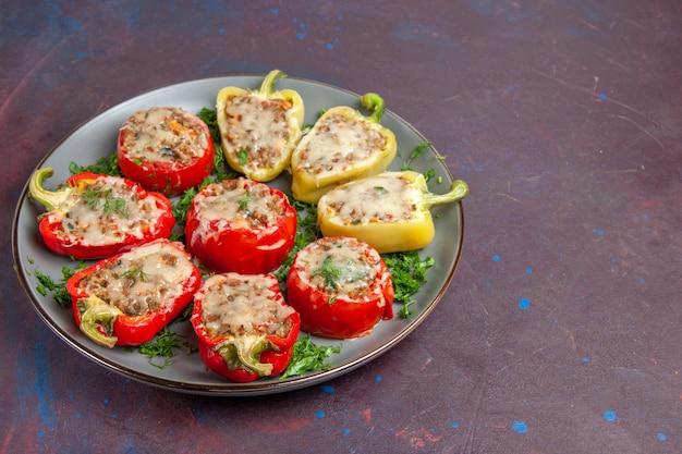 Vista frontale peperoni al forno con verdure al formaggio e carne all'interno del piatto sullo sfondo scuro cuocere il pasto del piatto della cena
