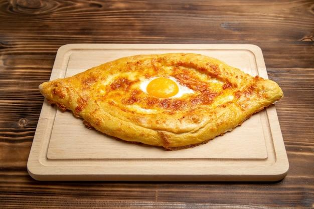 Vista frontale pane cotto con uovo cotto sulla superficie in legno pane panino cibo uovo pasta per la colazione