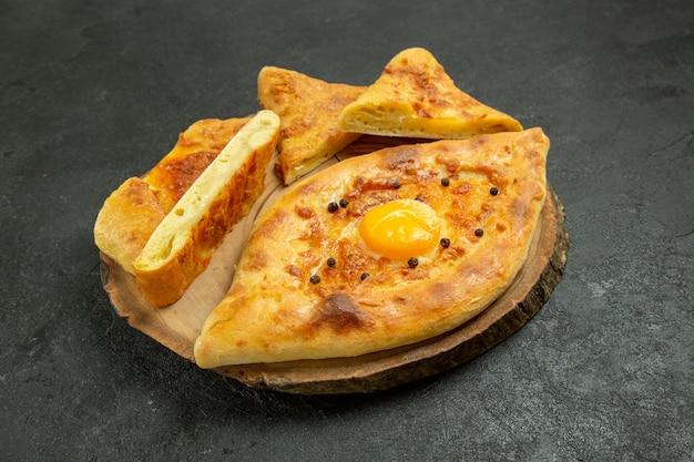 濃い灰色の空間でオーブンから焼きたてのおいしい焼き卵パンの正面図