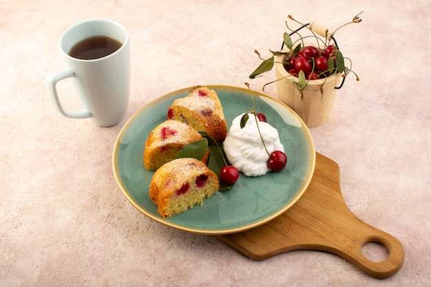 A front view baked fruit cake delicious sliced with red cherries inside and sugar powder inside round green plate with tea on pink