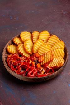 어두운 공간에서 조리 된 야채와 함께 구운 감자 전면보기