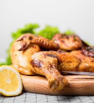正面図レモンとまな板の上に丸ごと鶏肉を焼いた