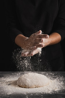 Front view baker spreading flour on dough composition