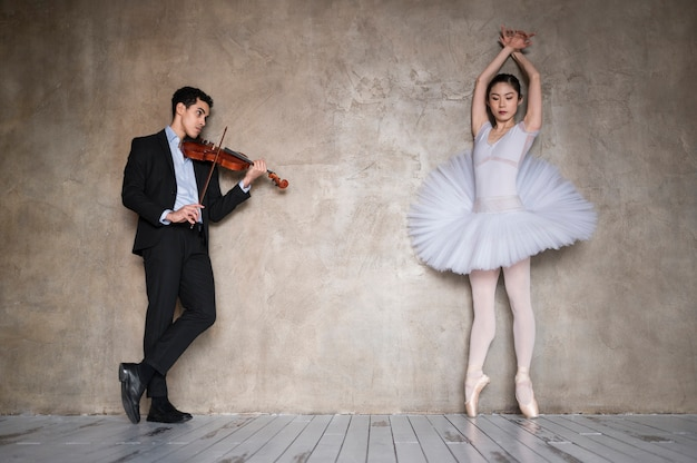 Front view of ballerina dancing to music played by male musician